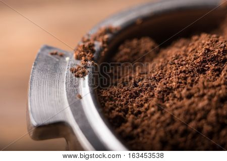 Ground coffee in porta filter holder, close up view.