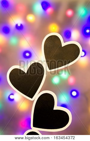Several black hearts against a colorful background
