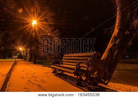 Bench on the illuminated winter park alley at night. Expectation. Possible date