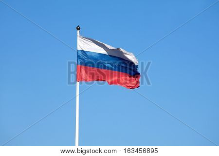 Russian flag on flagpole waving on a clear sunny day on a background of blue cloudless sky