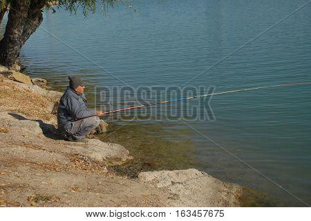 ADANA/TURKEY-DECEMBER 9, 2016:  Old fisherman at the riverside of Seyhan River of Adana. December 9, 2016-Adana/Turkey
