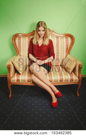 Attractive pretty young woman sitting on vintage retro sofa couch. Elegant fashionable gorgeous girl wearing maroon shirt and skirt. Fashion.