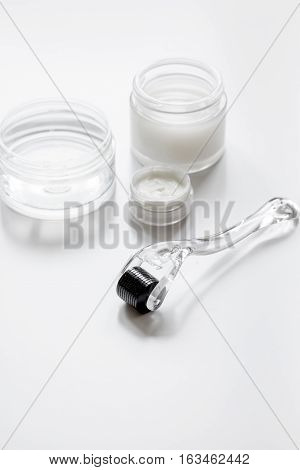 concept cosmetologist desktop with mezoroller - mesotherapy on white background.