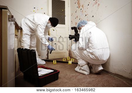 Team of criminologist technicians working on gun packing