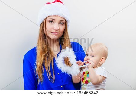 Christmas family holiday concept. Mother wearing santa claus hat holding and hugging baby.