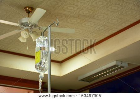 The saline bag and fan in hospital background