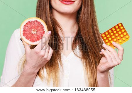 Woman holding pills blister pack vitamin c in one hand and grapefruit in another. Choice between natural and synthetic way of health care. Alternative medicine. Studio shot on green background