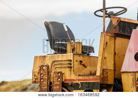 Agriculture harvesting gardening machinery concept. Combine harvester standing next to coutryside path on sunny day