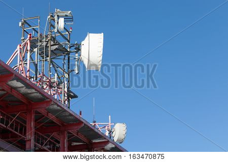 Telecommunications Tower With Several Antennas And Clear Blue Sky On Background