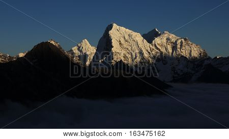 Evening scene in the Himalayas. Snow covered mountains just before sunset.