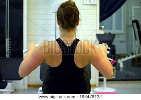 Woman workout her back muscles and arms with pulley at the gym.