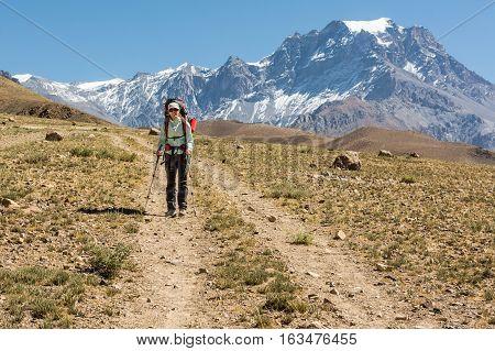Female trekker walking alone though mountain desert. Annapurna circuit trek in Nepal.