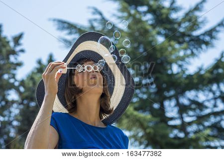 Stylish woman in a blue and white straw sunhat blowing soap bubbles outdoors in the garden as she celebrates the season low angle view against trees and blue sky.