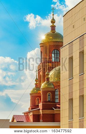 Sunny glitter of golden domes of the Cathedral displayed due to the corner of the building. Stroitel town.