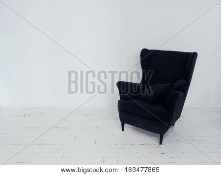 Soft armchair with decorative pillows Dark blue armchair standing in white room with wooden floor