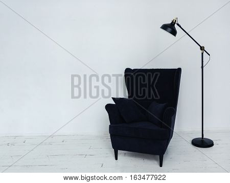 Soft armchair with decorative pillows Dark blue armchair with black floor lamp standing in white room with wooden floor