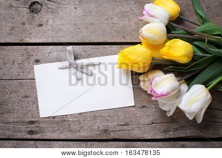 Yellow and white spring tulips and empty tag on vintage wooden background. Selective focus. Place for text