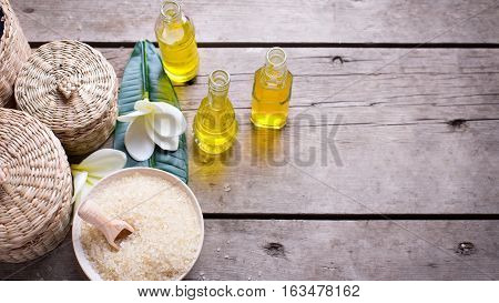 Spa set. Bottles with essential aroma oil sea salt and tropical flowers plumeria on wooden background. Selective focus.Place for text.