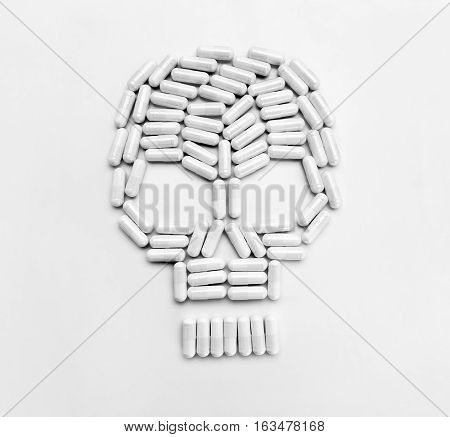 White capsules forming a skull symbol on gray background. Top view copy space high resolution product. Drug abuse concept