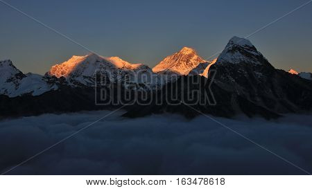 Mt Everest and other hight mountains of the Himalayas at sunset. Sea of fog.