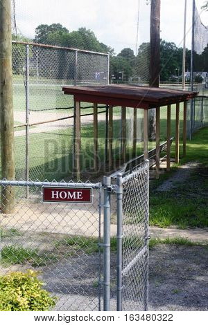 Empty home team wooden baseball dugout with fence