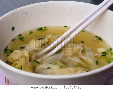 Wan Tan soup in white bowl and eating sticks