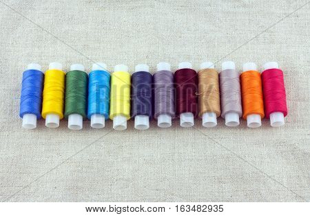 Long horizontal row of lot color thread spools on beige fabric background. front view closeup