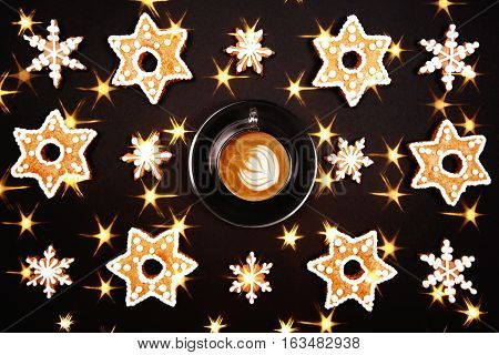 Background made with gingerbread. Christmas gingerbread. Cup of cappuccino with beautiful latte eart in the center of photo. Flat lay style.