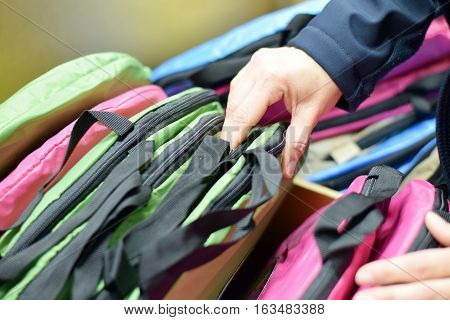 Woman's Hand Shopping Through Backpacks