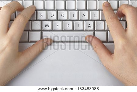 Hands typing on a keyboard. The keys spell out