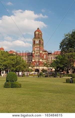 YANGON MYANMAR - NOVEMBER 26 2016: The red buildin of High Court Palace is listed on the Yangon City Heritage List. Located near Yangon City Hall the building faces the Independence Monument and the Maha Bandula Park.