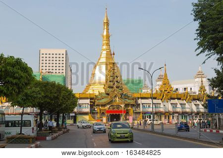 YANGON MYANMAR - NOVEMBER 26 2016: some cars and traffic in the downtown of Yangon Myanmar with the Sule pagoda in the background