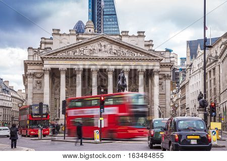 London England - Iconic red double decker busses on the move and black and green london taxies with the Royal Exchange building