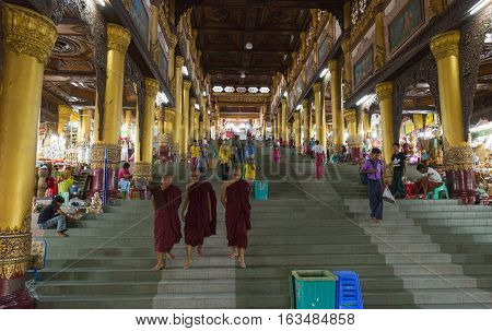 YANGON MYANMAR - NOVEMBER 26 2016: The west entrance of Shwedagon Pagoda with busy shops and people. Shwedagon is the most popular pagoda of southeast asia.