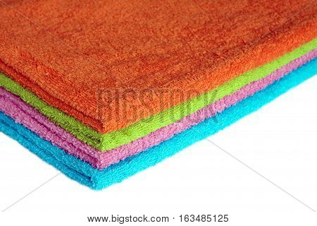 Four clean soft double bath towels set of different colors stacked isolated on white background. Side view from corner close-up