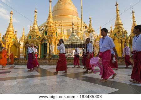 YANGON MYANMAR - NOVEMBER 26 2016: Ordination ceremony at the sunset in the Shwedagon pagoda with monks walking around the pagoda and carrying sacred items