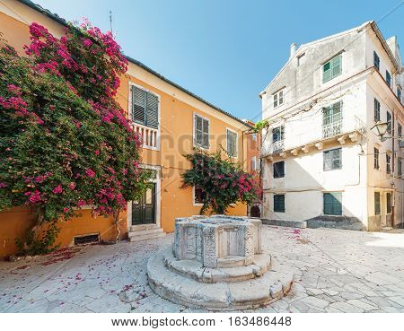 Courtyard with venetian well in the Old town of Corfu Greece