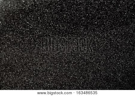 White flying snowflakes on the black background