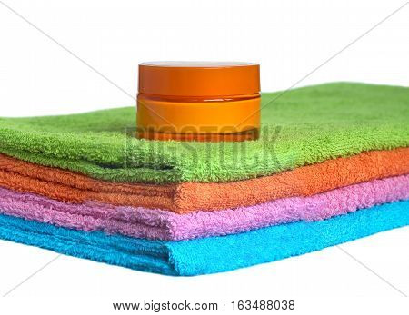Four clean soft double bath towels set of different colors stacked and jar of cosmetic skin cream isolated on white background. Side view from corner close-up