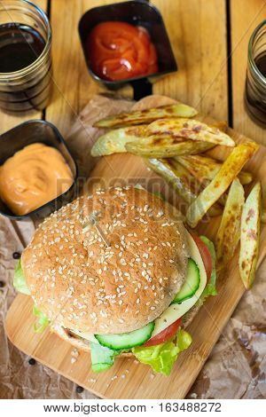 Hamburger with whole wheat buns vegetables and french fries