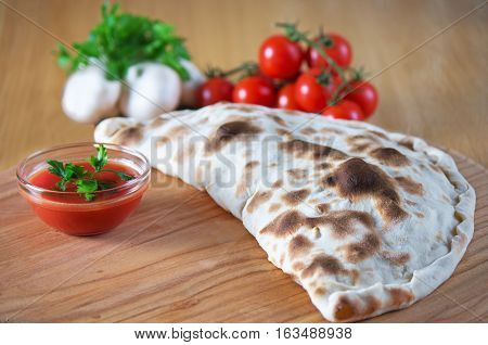 Pizza calzone with close up on a wooden background