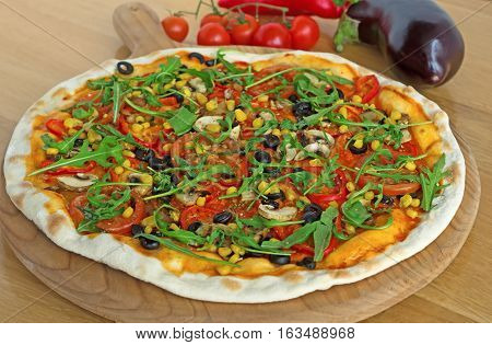 Fresh tasty pizza mushrooms, olives, arugula and tomatoes on wooden background