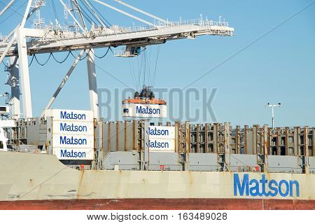 Oakland CA - December 28 2016: Matson cargo ship MAUI unloading at the Port of Oakland. Crane operators can move an average of 30 containers per hour on or off the ships.