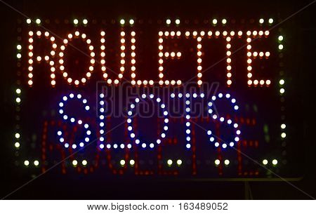 Roulette slots light sign on dark background advertising casino