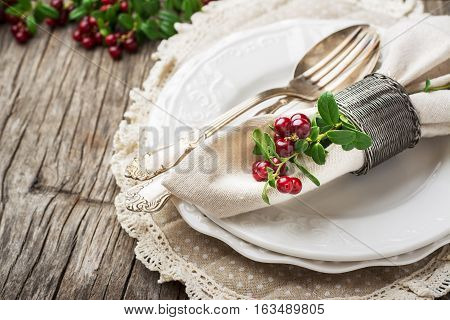 Serving for Thanksgiving, Christmas or New Year with berries cranberries on ceramic white plates with vintage German silver cutlery. Top view