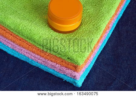 Four clean soft double bath towels set of different colors stacked and jar of cosmetic skin cream on table on denim cloth background. Top view from corner closeup