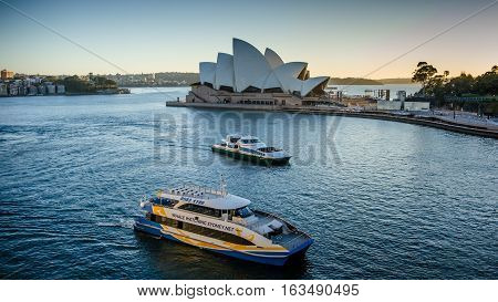 SIDNEY - AUSTRALIA NOVEMBER 2, 2016: Whale-watching boat for tourists sails past the Sidney Opera House, a multi-venue performing arts center, designed by Danish architect Jorn Utzon.