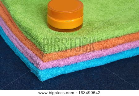 Clean soft double bath towels set of different colors stacked and jar of cosmetic skin cream on table on denim cloth background. Top view from corner close-up