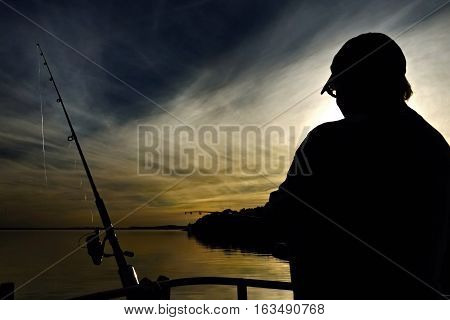 Silhouette of a lady fishing with a sunset over water through cloud at Fame Cove Port Stephens New South Wales Australia.