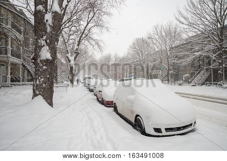 Snowstorm in Montreal. Cars covered with snow.